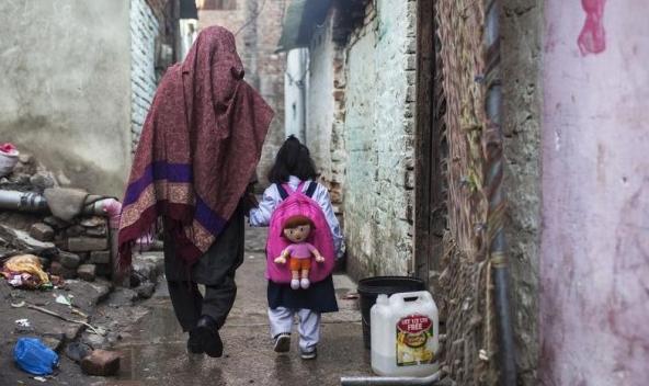 Uma mãe leva a filha para a escola em Islamabad