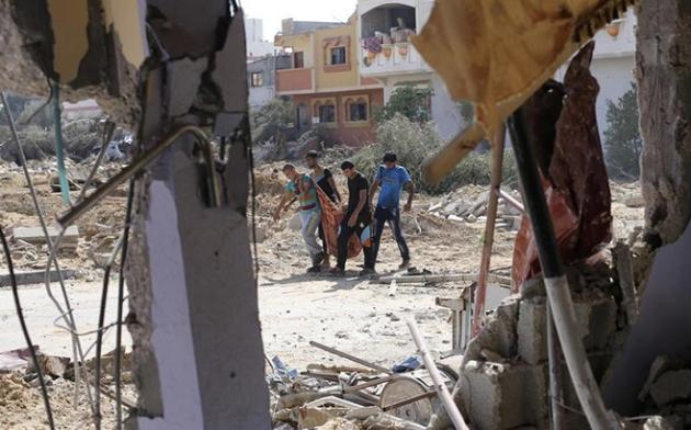 Palestinos carregam corpos de mortos, a leste de Khan Younis, no sul da Faixa de Gaza / Créditos: © 2014 Reuters